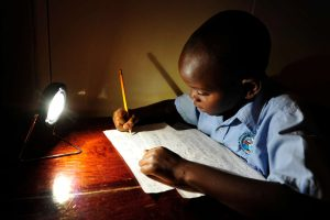 A young boy in Zambia does his homework by a solar-powered lamp. Photo by Patrick Bentley/SolarAid
